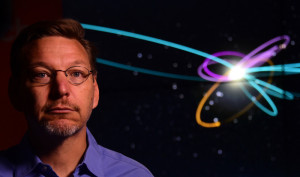 """Caltech Astronomer Mike Brown poses in front of a screen showing the """"Predicted Orbit"""", in yellow, of the 9th Planet at a Caltech Seismology Lab in Pasadena, California on January 20,2016. __Brown and his colleague, planetary scientists Konstantin Batygin, reported having """"good evidence"""" of the 9th planet on the fringes of our solar system. / AFP / FREDERIC J BROWNFREDERIC J BROWN/AFP/Getty Images"""
